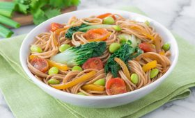 Ancient grains spaghettini with sesame bok choy and carrots on display in a white bowl