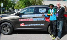 Yemane Tsegay and sponsor pose with Hyundai SUV
