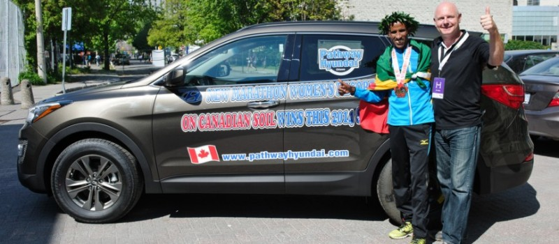 Yemane Tsegay and sponsor pose with Hyundai SUV